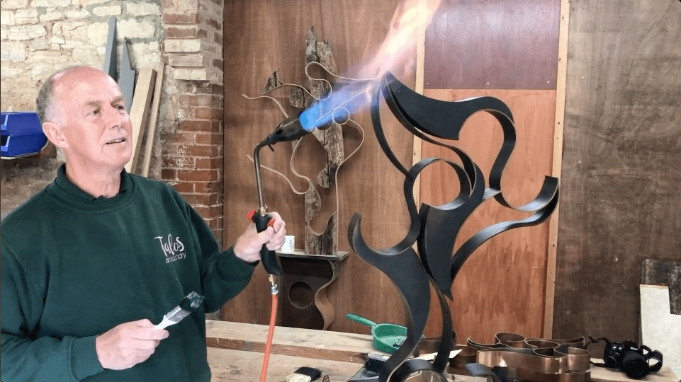 Richard fires up the blow torch to wax the bronze sculpture